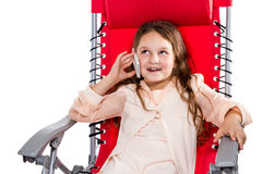 Girl talking on the phone sitting in an armchair Royalty Free Stock Photo