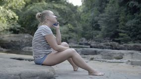 Girl talking on the phone sitting on the stone in nature. Slider. stock video footage