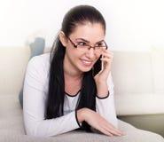 Girl talking on the phone on sofa Royalty Free Stock Photos