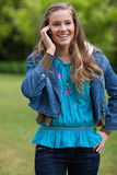 Girl talking on the phone while standing in a pa Royalty Free Stock Photography