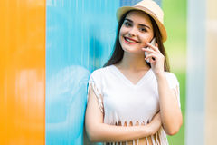 Girl talking phone on the street over color background Stock Photography
