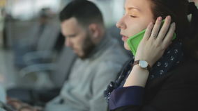 A girl talking on the phone and a young man using a tablet at the background. stock video