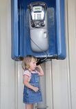Girl talking by public phone Royalty Free Stock Photo