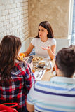 Girl talking seriously to her girlfriend at the restaurant. While male friend sitting across her stock image