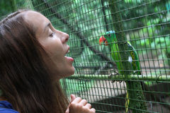 Girl talking to the parrot Royalty Free Stock Photography