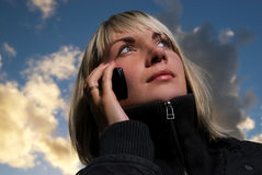 Girl talking to the phone. Over blue cloudy sky Royalty Free Stock Images