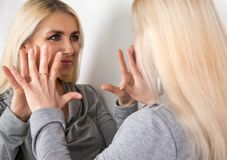 The girl is talking to yourself in the mirror. Royalty Free Stock Images