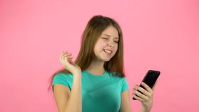 Girl talking at video chatting on cell phone in studio against pink background. Girl talking at video chatting on the cell phone in studio against pink stock footage
