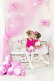 Girl talking whispering secret to friend in birthday party. Present to sister pink gift boxes stock photography