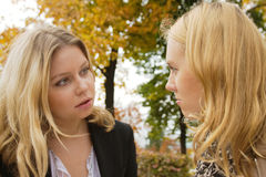 Girl talks. Two blond girls having serious conversation outdoors Royalty Free Stock Photography