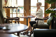 Girl talks on cell in cafe Stock Photos