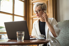 Girl talks on cell in cafe Royalty Free Stock Image