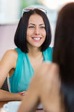 Girl talks with friend sitting at the cafe Stock Photography