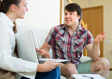Girl talks with man while interviewing him at home Stock Image
