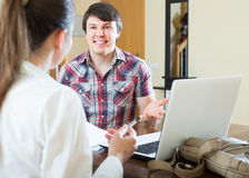 Girl talks with man while interviewing him at home Stock Photos