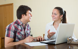 Girl talks with man while interviewing him at home Royalty Free Stock Image