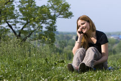 Girl Talks By A Mobile. The young girl talks by a mobile phone. Outdoor Royalty Free Stock Photo