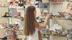 Girl talks on the phone at the shoe shop stock footage