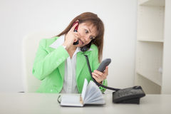 Girl talks by several phones simultaneously Stock Image