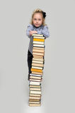 Girl and a tall stack of books Stock Photography