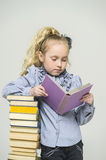 Girl and a tall stack of books Royalty Free Stock Photos