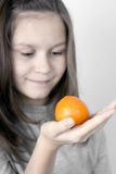 The girl and a tangerine Stock Photos
