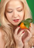 Girl with tangerine Royalty Free Stock Images