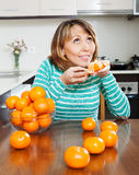 Girl with tangerines in home kitchen Royalty Free Stock Photo