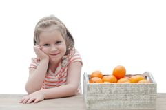 Girl and tangerines. Girl next to the box with tangerines stock image