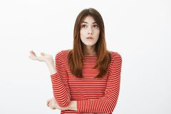 Girl tangle in thoughts. Portrait of clueless troubled european female student in striped red blouse, spreading palm and. Looking up with clueless unaware Stock Photos