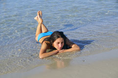 Girl tanning. Girl resting on the shore of a calm sea Stock Photo