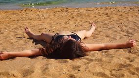 Girl tans on beach stock footage