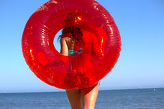 Girl with Target Red Inner tube on Beach. Teen with red inner tube on beach with blue sky and sea in background Stock Photos