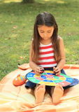 Girl with target. Sitting little barefoot girl playing with a colorful target stock photo
