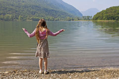 Girl at tarn. A seven years old girl is enjoying a morning at a small lake called Lago di Piano in Italy Royalty Free Stock Image
