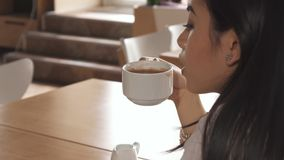 Girl tastes coffee at the cafe. Pretty asian girl tasting coffee at the cafe. Close up of attractive brunette lady removing her hair behind her ear. Camera stock image