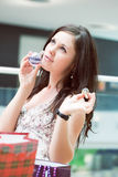 Girl tastes a smell just the spirits bought. In shopping center Stock Photography