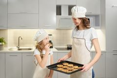 Girl tasting homemade american cookies cooked by mother. stock photo