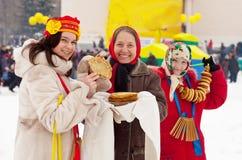 Girl tasting pancake  during  Shrovetide Royalty Free Stock Images