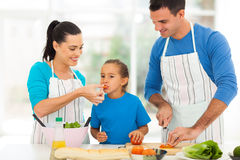 Girl tasting parents cooking stock photo