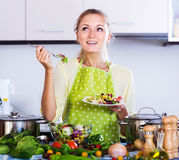 Girl tasting vegetable salad Royalty Free Stock Image