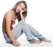 Girl with tattered jeans sit on floor Royalty Free Stock Photo