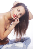 Girl with tattered jeans sit on floor. Attractive girl with tattered jeans sit on floor Royalty Free Stock Image