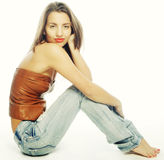 Girl with tattered jeans sit on floor Royalty Free Stock Photography