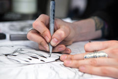 Girl tattoo artist draws a sketch. Close-up of hands Royalty Free Stock Photography