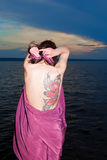 Girl with tattoo of butterfly on back in burgundy dress. Girl with tattoo of butterfly back in burgundy dress on bay stock image