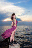 Girl with tattoo of butterfly on back in burgundy dress. Girl with tattoo of butterfly back in burgundy dress on bay concrete structures royalty free stock photography