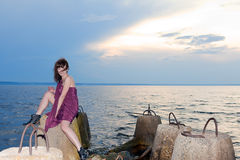 Girl with tattoo of butterfly on back in burgundy dress. Girl with tattoo of butterfly back in burgundy dress on bay concrete structures stock photography