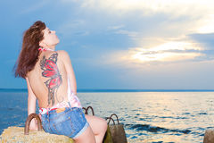 Girl with tattoo of butterfly on back of gulf shore. With concrete structures royalty free stock images