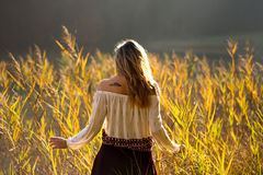 Girl with tattoo mountains on the shoulder standing and meditating in field of reeds / Blond girl walking through field of reeds. Girl with tattoo mountains on stock photo